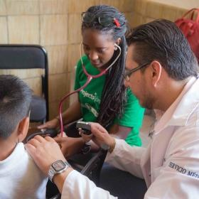 Medical interns in Mexico help at an outreach alongside a local doctor.